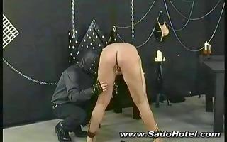 dark brown slave is tortured by her masked
